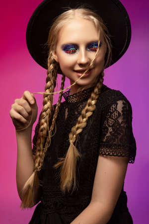 A beautiful smiling blonde teenage girl wearing a black gothic dress and a black hat. Conceptual makeup, red eyelashes and sequins. Healthy smooth skin. Pink and violet background. Copy space.