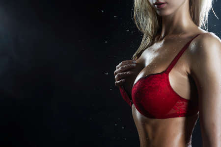 Close Up photo of wet hot and sweaty sensual big tits of tanned athletic blonde girl wearing red bra under falling water drops of rain on black. Healthy smooth skin. Copy space. Advertising design. Archivio Fotografico