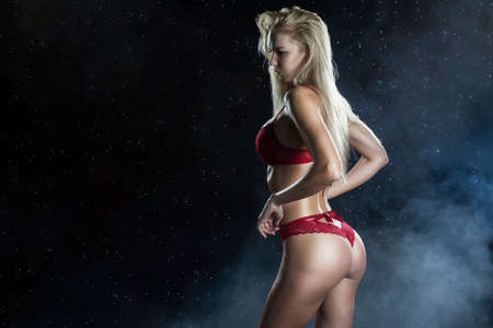 Beautiful wet sporty big tits tanned blonde girl wearing red underwear posing sideways in scenic smoke and fog under falling water drops of rain on black. Healthy smooth skin. Copy space. Stock Photo
