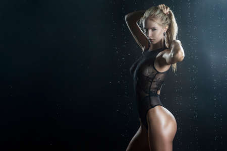 Beautiful shapely athletic big breasted  blonde girl with wet oiled body wearing black translucent sexy bodysuit posing sideways in scenic smoke under falling water drops of rain on black. Copy space Stock Photo