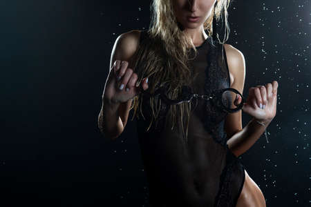 Close up photo of athletic blonde girl wearing black sexy translucent bodysuit with wet oiled skin, holds handcuffs in her hands, posing under falling water drops on black background. Copy space.