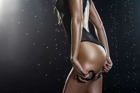 Close up photo of athletic blonde girl wearing black translucent bodysuit with wet oiled sexy butt, holds handcuffs in her hands standing with her back under falling water drops on black. Copy space.