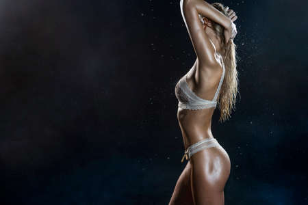 Beautiful wet athletic big breasted blonde girl wearing white sexy translucent bikini posing in falling water drops of rain on black background. Healthy smooth skin. Copy space. Advertising design.