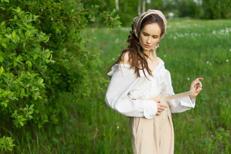 Beautiful stylish young girl wearing a trendy white shirt, beige trousers, and a pareo on her hair poses outdoors against a meadow and trees. Commercial and advertisement design. Copy space