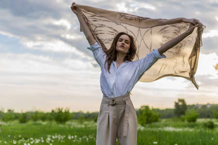 Beautiful stylish girl wearing a trendy white shirt, beige trousers and a pareo poses outdoors against a background of meadow full of wild flowers and blue cloudy sky. Advertising design. Copy space.