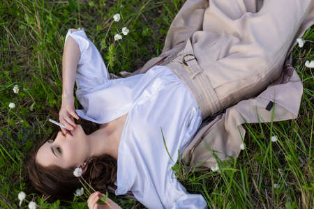 Beautiful stylish young girl wearing a trendy white shirt, beige bloomers, and a pareo lies relaxing on the green grass among the wild flowers and smoking cigarette. Advertisement design. Copy space.