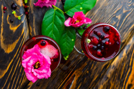 Two glasses full of red drink with berries, ice and a pink flowers, beside which lie berries and a branch of green tropical leaves on a vintage wooden table. Copy space. Commercial design.