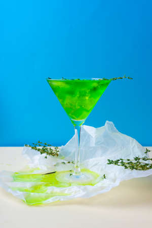 A green drink with ice cubes and green branches in a glass for mojito on crumpled wrapping paper on yellow table and blue background. Conceptual and advertising design. Copy space. Фото со стока