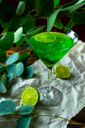 A green drink with ice cubes in a glass for mojito on crumpled wrapping paper next to which lie slices of lime and a branch of green tropical leaves on a vintage wooden table. Copy space.