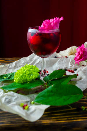A glass full of red drink with berries, ice and a pink flower on crumpled wrapping paper beside which lie berries and a branch of green tropical leaves on a vintage wooden table. Copy space.