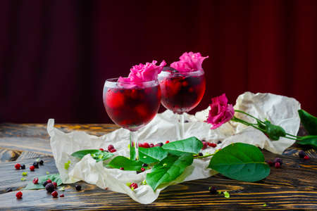 Two glases full of red drink with berries, ice and a pink flowers on crumpled wrapping paper beside which lie berries and a branch of green tropical leaves on a vintage wooden table. Copy space.