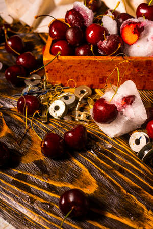 Frozen iced and fresh red cherry in a glass next to a vintage wooden box on an ancient wooden table on which spools of thread are scattered. Conceptual close-up photo. Copy space. Advertisement design