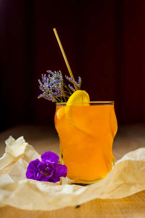 Figured glass of yellow fruit juice with a slice of lemon, a green branch of small flowers and a purple flower beside, on crumpled wrapping paper on a wooden table. Commercial design. Copy space. Фото со стока