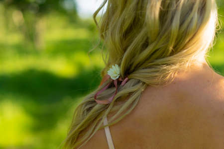 Close up photo from the back of blonde girl hair with a flower braided in them. Girl wearing pink underwear lingerie. Lifestyle summer photo. Advertising, commercial and conceptual design. Copy space. Фото со стока