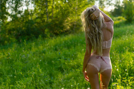 Beautiful blonde slim girl with a nice ass wearing pink lingerie and a ribbon on her sexy body stands with her back turned in the park. Summer lifestyle photo. Commercial design. Copy space. Stock Photo
