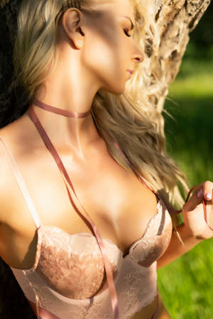 Beautiful sexy blonde slim girl wearing pink lingerie and a ribbon on her neck stands with her back to the old tree and passionately curves. Summer lifestyle photo. Advertising and conceptual design. Фото со стока