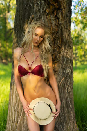 Beautiful blonde sexy slim girl ass wearing only red bra without a panties passionately bending, is leaning her back against the tree trunk and shyly covering her nakedness with her hat. Copy space. Фото со стока