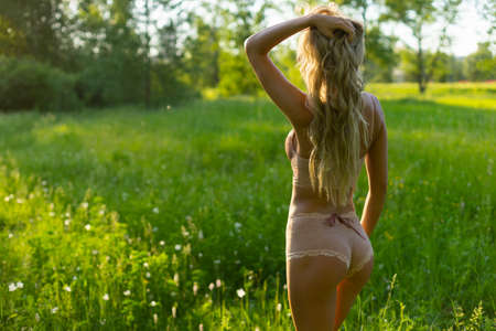 Beautiful blonde slim girl with a nice ass wearing pink lingerie and a ribbon on her sexy body stands with her back turned in the park. Summer lifestyle photo. Commercial design. Copy space. Standard-Bild