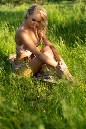 Beautiful blonde slim girl wearing pink lingerie sits alone outdoor on the grass in the park. Summer sunny lifestyle photo. Advertising and conceptual design. Copy space.