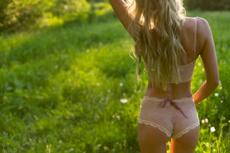 Beautiful blonde slim girl with a nice ass wearing pink lingerie and a ribbon on her sexy body stands with her back turned in the park. Summer lifestyle photo. Commercial design. Copy space. Фото со стока
