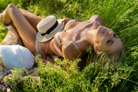 Blonde slim girl wearing pink lingerie holds a hat and lays on the grass and passionately curves, enjoying the sun. Summer sunny lifestyle photo. Advertising and conceptual design. Copy space. Фото со стока