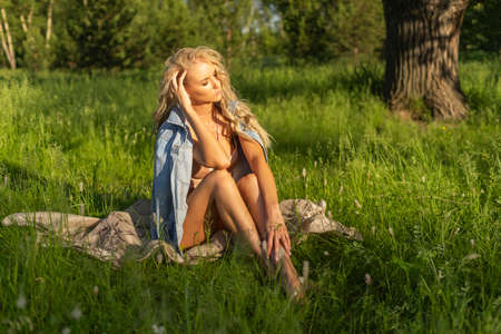 Beautiful blonde slim girl wearing pink lingerie and jeans jacket sits on the grass in the park outdoors. Summer sunny lifestyle photo. Advertising and conceptual design. Copy space.
