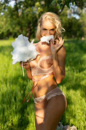 Beautiful blonde slim girl wearing pink lingerie walks outdoor in the park and eats candy floss and have fun. Summer sunny lifestyle photo. Advertising and conceptual design. Copy space.