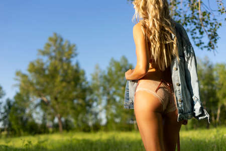 Beautiful blonde slim girl with a beautiful ass wearing pink lingerie and jeans jacket walks in the park outdoors. Summer sunny lifestyle photo. Advertising and conceptual design. Copy space.