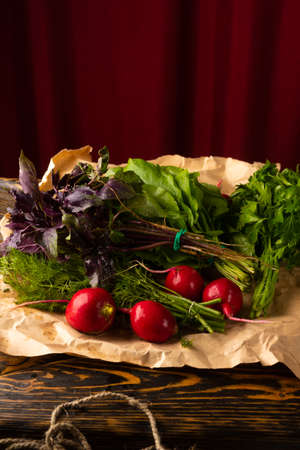 Bunches of fresh herbs of parsley, dill, basil, radish and sorrel lie on a plate covered a wrapping paper an old wooden table. Copy space. Advertising design. Kitchen, restaurant, cooking Фото со стока
