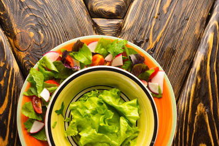 A beautiful serving of leaves of fresh lettuce, sorrel leaves, a slice of cherry tomatoes and radish in two plates on an old wooden table. Copy space. Advertising design. Kitchen, restaurant, cooking.