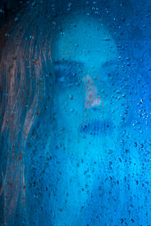 Art style portrait in blue tones of a lonely beautiful sad model girl behind a window glass, over which rain drops down. Conceptual, commercial and fashionable design. Copy space.