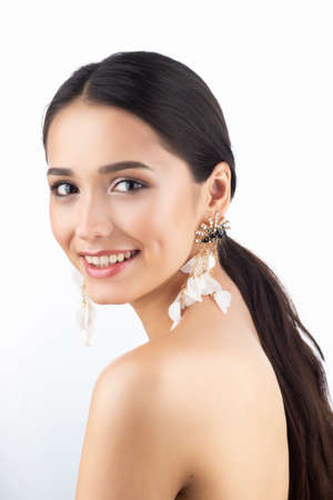 Beauty portrait of a beautiful smiling brunette girl model with bare shoulders and brown eyes wearing earrings imitation jewelry isolated on white background. Commercial design. Copy space.