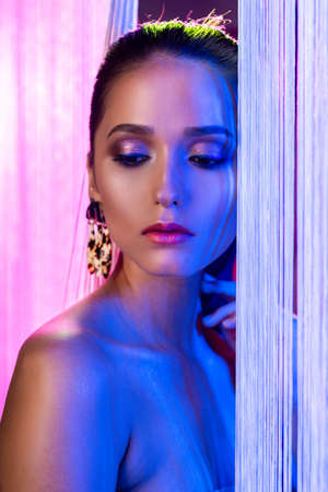 A beautiful glamorous brunette girl with naked shoulders wearing large elegant earrings peeps through a translucent curtain made of white threads. Multicolored artistic stage lighting. Copy space.