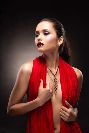 Beautiful brunette topless girl model, covering her naked breast with a red scarf and wearing a modern necklace on the deep decollete. Copy space. Advertising and commercial design. Healthy clean skin Reklamní fotografie