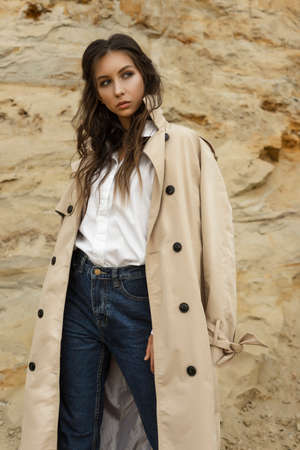 Beautiful girl wearing blue jeans, a white blouse and a beige raincoat posing in a sandy quarry against the backdrop of a sand wall. Healthy clean skin. Commercial, fashionable and advertising photo