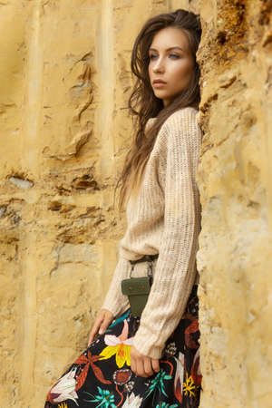 Beautiful girl wearing a beige sweater and a black skirt with a pattern in the form of large flowers posing in a sandy quarry. Advertising, lifestyle, fashion and commercial design. Copy space.
