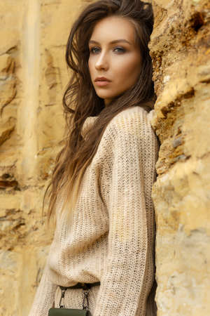 Beautiful girl wearing a beige sweater and a black skirt with a pattern in the form of large flowers posing in a sandy quarry. Advertising, lifestyle, fashion and commercial design. Close-up portrait. Stock Photo