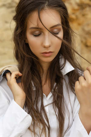 Artistic style close-up portrait of a beautiful girl with closed eyes and wearing a white blouse in a sandy quarry. Healthy clean skin. Advertising and commercial design. Stock Photo