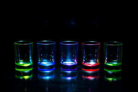 Five multicolored empty shot glasses reflecting on a glass surface symmetrically placed a black background. Conceptual, commercial and advertising photo. Copy space.