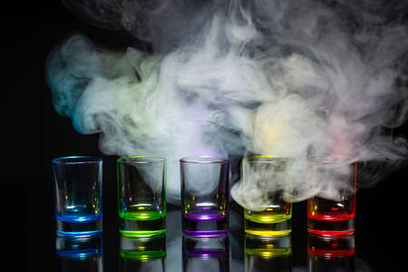 Five multicolored empty shot glasses placed symmetrically on a black background in a theatrical smoke. Conceptual, commercial and advertising photo. Copy space. Stok Fotoğraf
