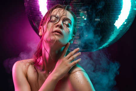 Beautiful girl with creative makeup made of glitter with tears on her face illuminated with pink and blue light in a scenic smoke near the big mirror ball on pink. Commercial design. Copy space.