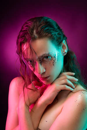 Beautiful girl with creative makeup made of glitter with tears on her face illuminated with pink and blue light. Pink background. Conceptual, advertising and commercial design. Copy space.