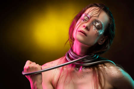 Beautiful girl with cretative make-up made of glitter with tears on her face wraps her neck with a metallic spiral hose illuminated with pink and yellow light. On yellow background. Copy space. Фото со стока