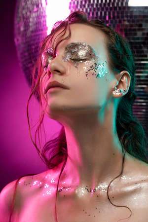 Beautiful girl with creative makeup made of glitter with tears on her face illuminated with pink and blue light near the big mirror ball on pink. Commercial and conceptual design. Copy space. Фото со стока