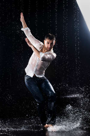 A young barefoot man wearing wet blue jeans and a white shirt expressively dances modern dances on the water under rainy waterdrops among the watersplashes. Isolated on a black background. Copy space.
