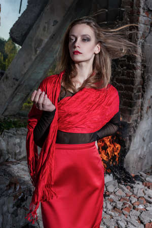Beautiful fashion model girl wearing a red long skirt and a red shawl stands near the burning brick walls of ruins of collapsed building. Conceptual, fashionable, modern and advertising design. Фото со стока
