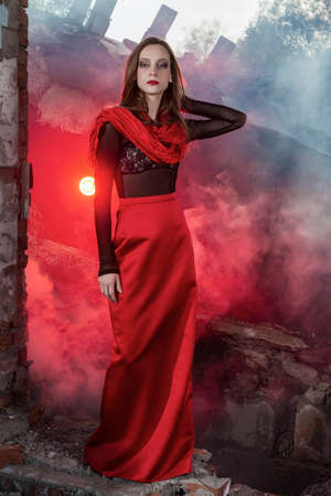 Beautiful fashion model girl wearing a red long skirt and a red shawl poses at the collapsed building, among the ruins of which rises red smoke. Conceptual, fashionable, modern and advertising design.