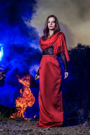 Beautiful fashion model girl wearing a red long skirt and a red shawl stands near the big fire in the background of blue smoke in sunset. Conceptual, fashionable, modern and advertising design.