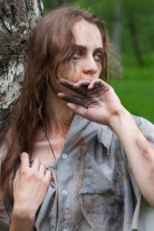 Beautiful young dirty mad and manic looking girl wearing torn clothes and smeared with mud and dried blood stands and huddles to a tree and wipes her face with her hand in the forest. Concept design.