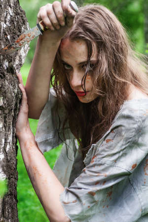 Beautiful young dirty mad and manic looking girl wearing torn clothes and smeared with mud and dried blood holds her hand to the knife stuck into tree in the forest. Copy space. Concept design. Фото со стока